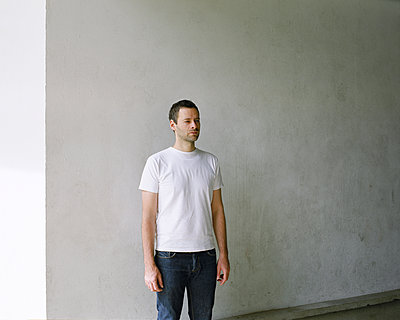 Mann steht vor einer weißen Wand - p1409m1466418 von margaret dearing