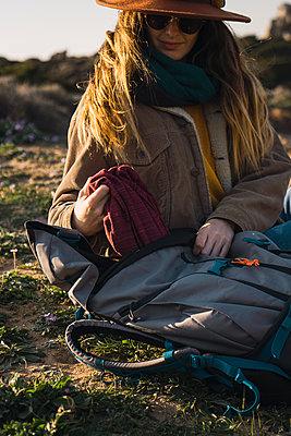 Italy, Sardinia, woman on a hiking trip having a break taking something out of backpack - p300m1580900 von Kike Arnaiz