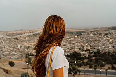 Redheaded woman enjoying city view in the evening, Fez, Morocco - p300m2159825 von VITTA GALLERY