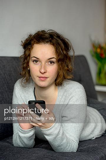 Junge Frau mit Smartphone auf dem Sofa - p1212m1217371 von harry + lidy