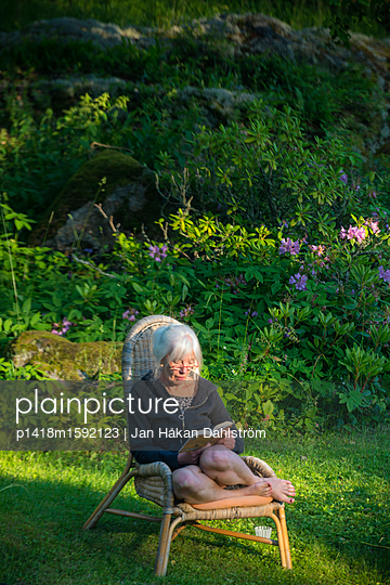 Frau liest Buch im Garten - p1418m1592123 von Jan Håkan Dahlström