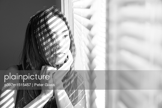 Young Asian woman sitting by a window - p397m1515457 by Peter Glass