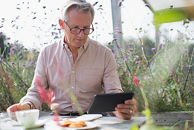 Senior man using digital tablet and drinking coffee at patio table - p1023m1475610 by Sam Edwards