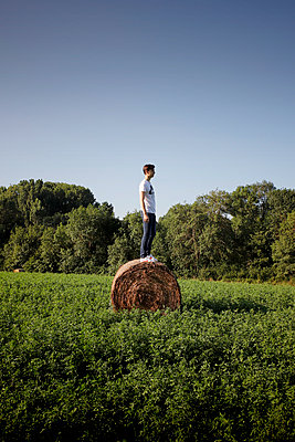 Young man on a hay bale - p1105m2288362 by Virginie Plauchut