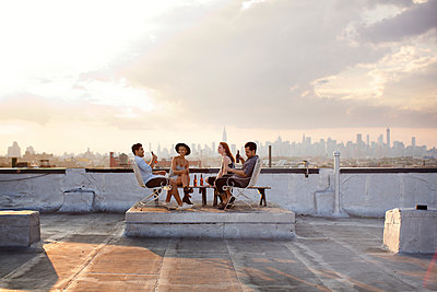 Happy friends enjoying while having beer at building terrace during sunset - p1166m1096854f by Cavan Images