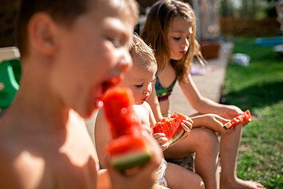 Siblings eating watermelons while sitting at yard - p1166m2009518 by Cavan Images