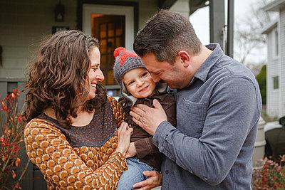 A joyful child is being tenderly held between his mom and dad in yard - p1166m2112928 by Cavan Images