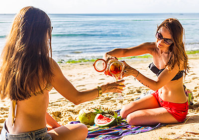 Two girls have a fun with sangria at the beach. - p1424m1500579 by Konstantin Trubavin