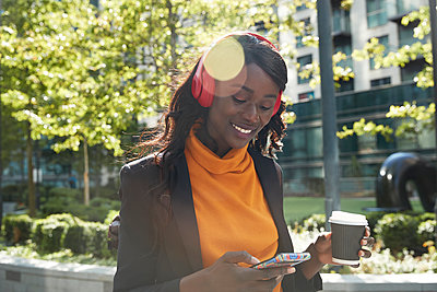 Smiling businesswoman using mobile phone while listening music on sunny day - p300m2241042 by Pete Muller