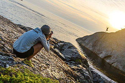 Photographer at coast, photographing friend in distance, Ontario, Canada - p924m2237503 by Alex Eggermont