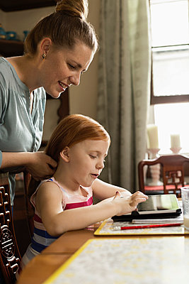 Girl using digital tablet at dining room table whilst mother styling her hair - p924m957987f by Roberto Westbrook