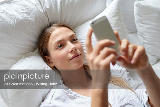 Junge Frau mit Smartphone auf dem Sofa - p1124m1589385 von Willing-Holtz