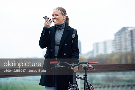 Smiling woman talking on mobile phone while holding bicycle against sky - p300m2256047 by Josep Suria
