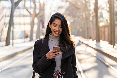 Smiling young woman with smartphone on tram line - p300m2166178 by VITTA GALLERY