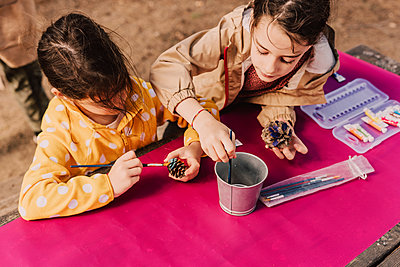 Sisters coloring pine cones at picnic table in park - p300m2225452 by Eloisa Ramos
