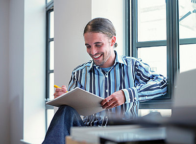 Smiling businessman writing in office - p42914331f by Colin Hawkins