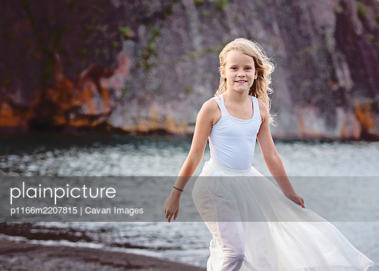 Young Blond Girl Dancing on Beach - p1166m2207815 by Cavan Images