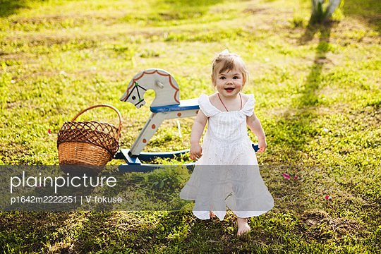 Little girl walks on grass with rocking horse in background - p1642m2222251 by V-fokuse