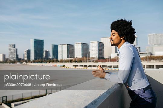 Spain, Barcelona, man leaning on balustrade enjoying sunlight - p300m2070448 by Josep Rovirosa
