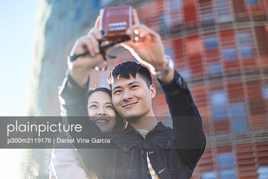 Portrait of couple talking selfie with instant camera, Barcelona, Spain - p300m2119176 by Daniel Vine Garcia