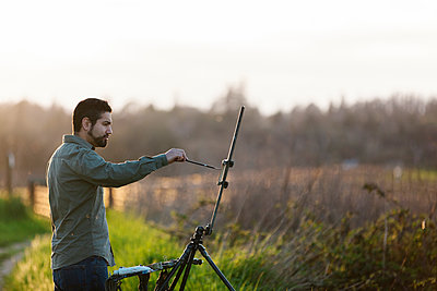 Side view of painter painting on canvas at field - p1166m1473624 by Cavan Images