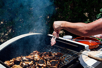 Hand of young man placing meat on barbecue grill in yard - p300m2206752 by Jose Luis CARRASCOSA
