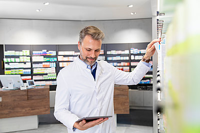 Male pharmacist doing inventory with digital tablet - p300m2251872 by Florian Küttler