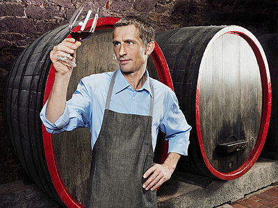A vintner studying red wine in a glass - p3018507f by Paul Hudson