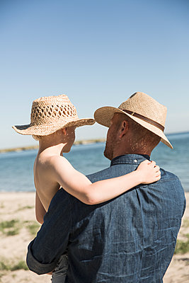 Sweden, Gotland, Mature man holding boy (8-9) at seashore - p352m1187041 by Jenny Lagerqvist