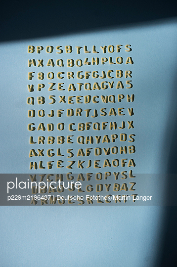 Yellow letters arranged on blue wall - p229m2196487 by Martin Langer