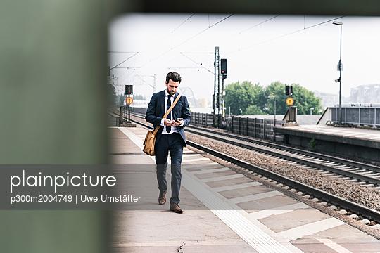 Businessman with cell phone walking at the platform - p300m2004749 von Uwe Umstätter