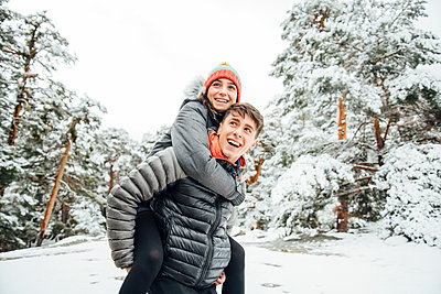 Portrait of happy young man giving his girlfriend a piggyback ride in winter forest - p300m2144271 von Oscar Carrascosa Martinez