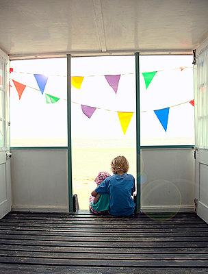 Boy and girl (6 -10) sitting on steps of a beach hut, Southwold, Suffolk, United Kingdom - p300m2298740 von LOUIS CHRISTIAN