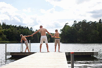 Rear view of pre-adolescent boys standing with father at the edge of boardwalk - p426m747615f by Maskot