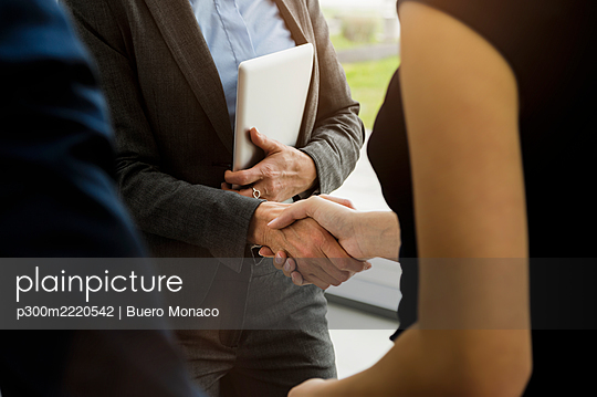 Close-up of business people giving handshake in office - p300m2220542 by Buero Monaco
