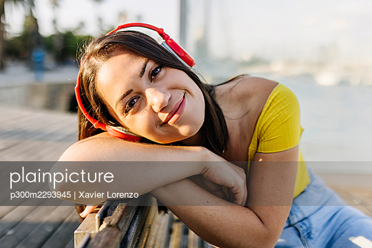 Young woman listening music through headphones while leaning on bench - p300m2293945 by Xavier Lorenzo