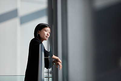 Pensive businesswoman looking through sunny office window - p1023m1121400f by John Wildgoose