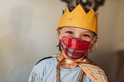 School aged young boy in dressed as king with face mask - p1166m2207780 by Cavan Images