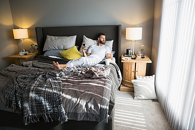 Relaxed man drinking coffee and using cell phone in morning bed - p1192m1201965 by Hero Images