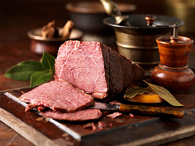 Christmas dinner. Dry cured pieced salt beef joint with  orange leaves - p429m974487f by Diana Miller