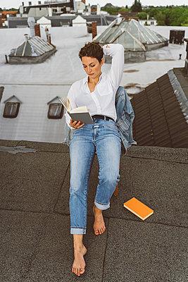 Frau liest ein Buch auf Dach - p432m2185653 von mia takahara