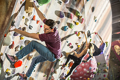 Athletes climbing rock wall in gym - p555m1411952 by John Fedele