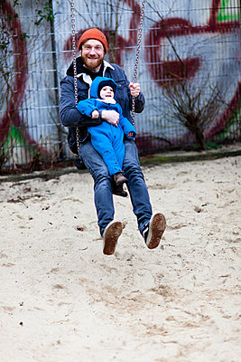 Father with happy son swinging together on a playground - p795m2192235 by JanJasperKlein