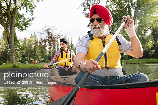 Mature Indian man canoeing with son - p1192m2129819 by Hero Images
