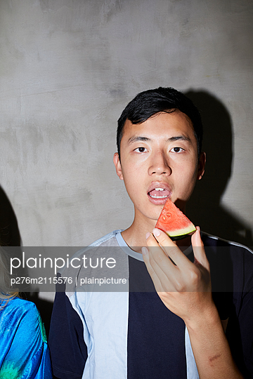 Young man with piece of melon - p276m2115576 by plainpicture