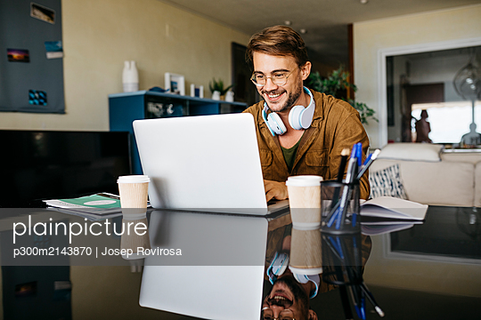 Smiling man working on table at home using laptop - p300m2143870 by Josep Rovirosa