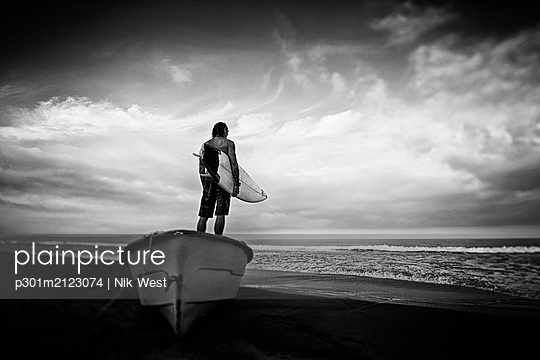 Male surfer with surfboard standing on beached boat, Higuera Blanca, Nayarit, Mexico - p301m2123074 by Nik West