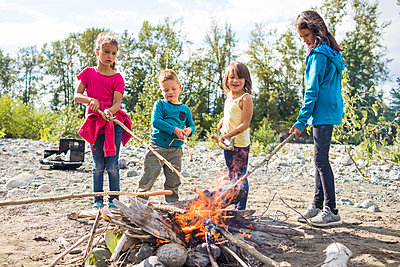 Group of children roasting hot dogs over campfire - p1166m2202008 by Christopher Kimmel / Alpine Edge Photography