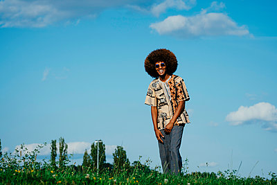 Portrait happy young man with afro in park grass - p301m2075533 by Sven Hagolani
