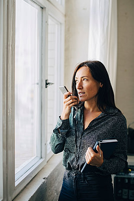 Creative businesswoman talking on mobile phone while standing by window in office - p426m2045989 by Maskot